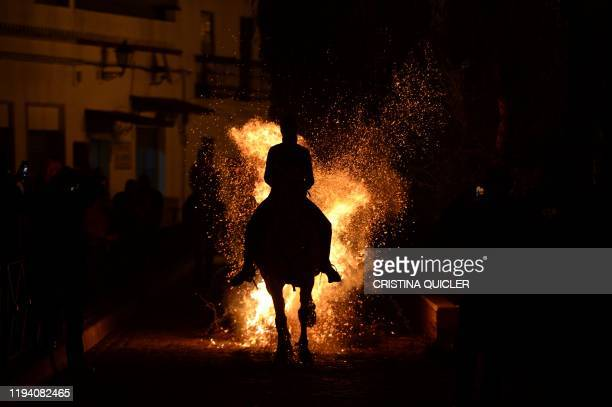 A horseman jumps over a bonfire in the village of Alosno near Huelva during the opening of the traditional religious festival Luminarias in honour of...