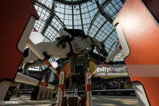 A horseman performs during 'Le Saut Hermes' horse jumping show under the glass canopy of the Grand Palais in Paris on March 22 2019
