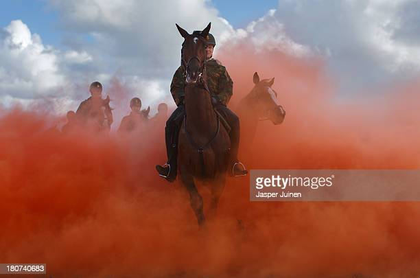 A horseman rides his horses through colored smoke during a practice session at the beach of Scheveningen on September 16 2013 in Scheveningen...