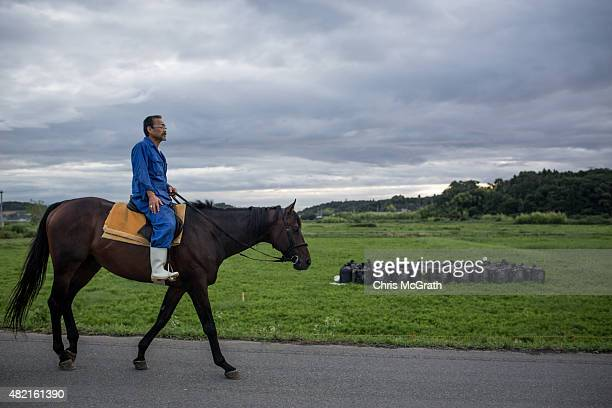 A horseman rides past bags of radiated soil left on the side of the road while taking his horse out for a training session ahead of the Soma Nomaoi...