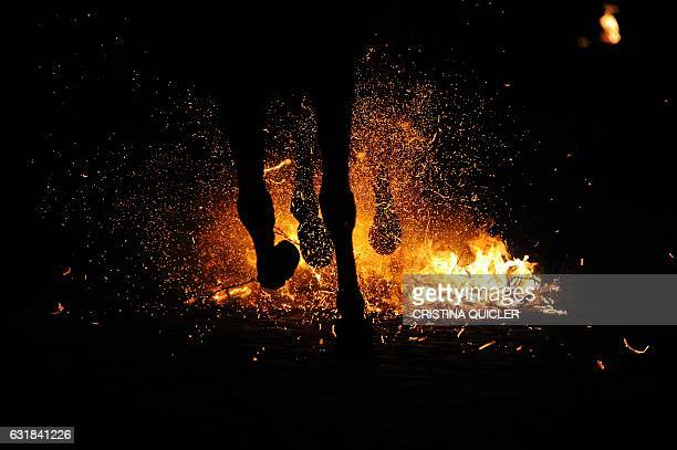 TOPSHOT A horseman rides through a bonfire during the celebrations of the traditional religious festival Luminarias in honour of San Antonio Abad...