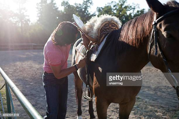 Horseman tuning a saddle on his horse before training session