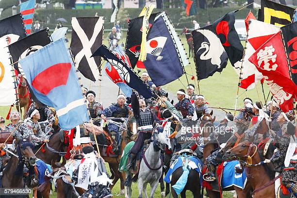 Horsemen dressed like samurai warriors compete to grab sacred flags shot into the air with fireworks at the Hibarigahara field in the city of...