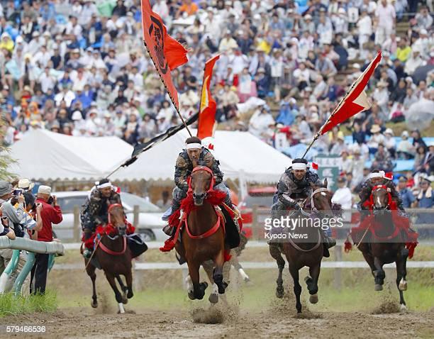 Horsemen dressed like samurai warriors dash on a 1,000-meter circuit at the Hibarigahara field in the city of Minamisouma, Fukushima Prefecture,...