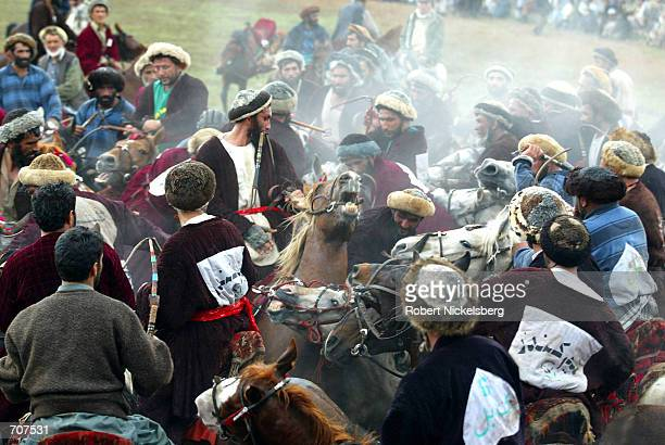 Horsemen from the Kabul Baglan Panjshir and Kunduz regions chase after a headless goat in the traditional game of buzkashi March 22 2002 in Kabul...