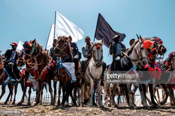 Horsemen hold black and white flags during a memorial ceremony at the crash site of the Ethiopian Airlines Flight 302 airplane accident in Tulu Fara...