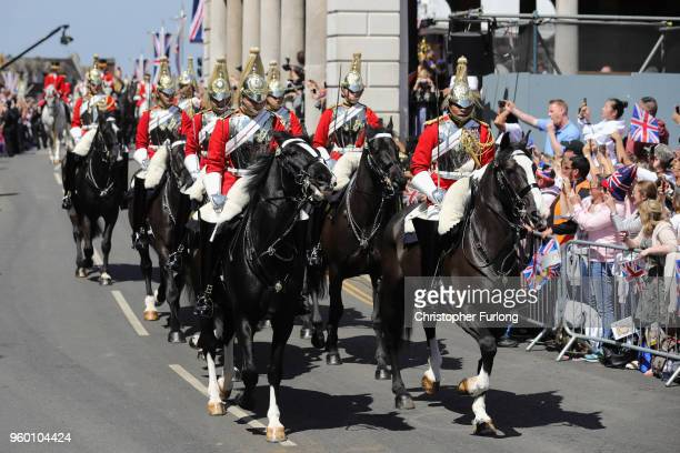 Horsemen lead Prince Harry Duke of Sussex and Meghan Duchess of Sussex as they leave Windsor Castle in the Ascot Landau carriage during a procession...