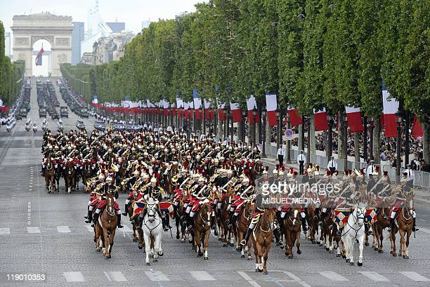 Horsemen of the French Republican guard ride their horses down the ChampsElysees with the arc de Triomphe in the background during the annual...