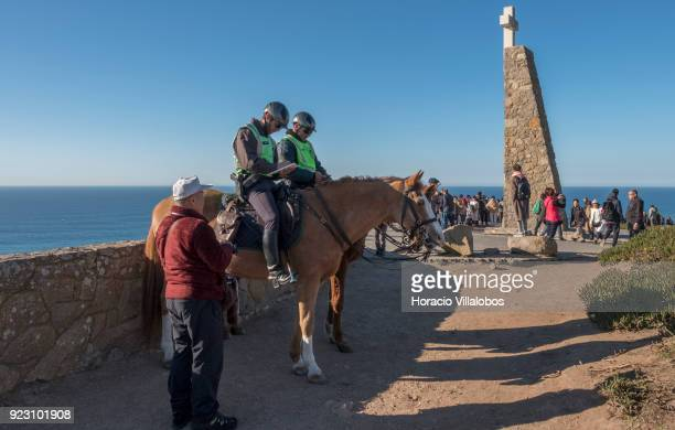 Horsemen of the National Republican Guard and tourists are seen on a sunny winter afternoon in Cabo da Roca on February 22 2018 in Sintra Portugal...