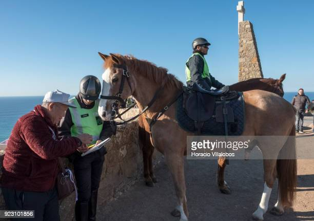 Horsemen of the National Republican Guard help a tourist on a sunny winter afternoon in Cabo da Roca on February 22 2018 in Sintra Portugal Cabo da...