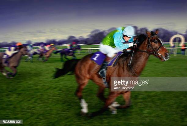 horseracing, jockey and mount passing finishing post (composite) - horse racing stock pictures, royalty-free photos & images