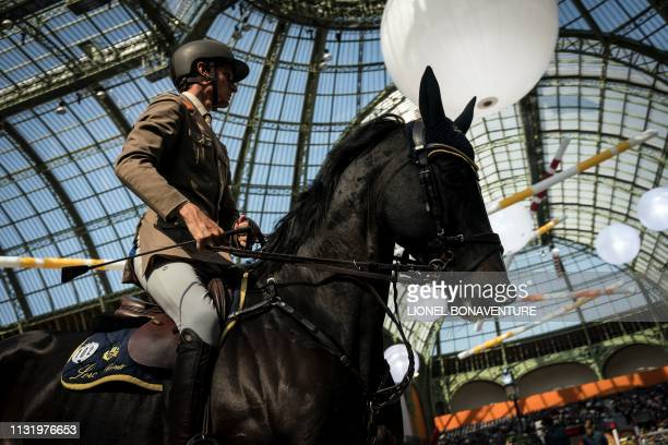 A horserider takes part in 'Le Saut Hermes' horse jumping show under the glass canopy of the Grand Palais in Paris on March 22 2019