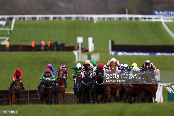 Horses and Riders clear a fence in the Coral Cup Handicap Hurdle during Cheltenham Festival Ladies Day at Cheltenham Racecourse on March 14 2018 in...