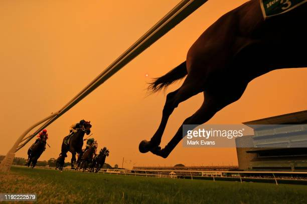 Horses and Riders compete in race 4 as a bushfire haze turns the sky orange during Sydney Twilight Racing at Royal Randwick Racecourse on December...