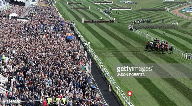 TOPSHOT Horses and riders in the The Gaskells Handicap Hurdle race go past the main stage during the final day of the Grand National Festival horse...