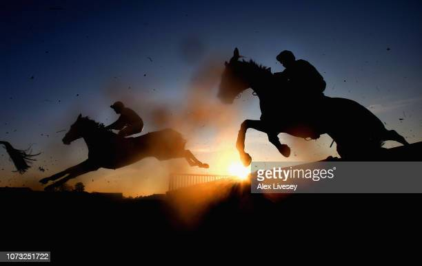 Horses and riders jump a fence during The Cliftons Of Wrexham Novices' Hurdle Race at Bangor Racecourse on December 14 2018 in Bangor Wales