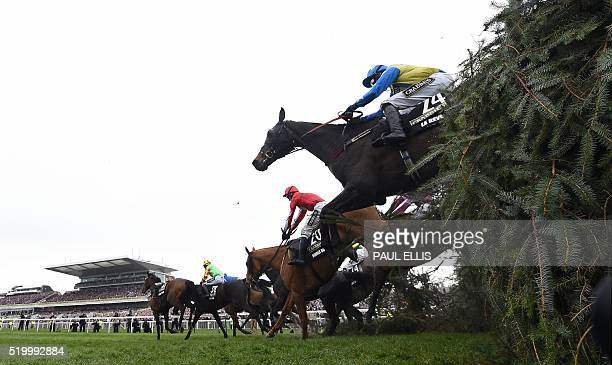 Horses and riders jump The Chair during the Grand National at Aintree Racecourse in Liverpool north west England on April 9 2016 Rule the World came...