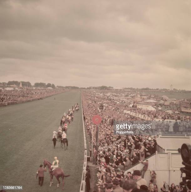 Horses and riders parade in front of spectators on the course prior to the start of the 1950 Epsom Derby at Epsom Downs Racecourse in Surrey, England...