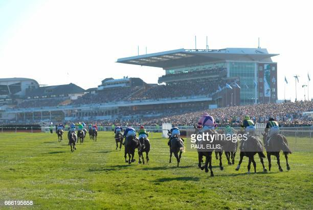 Horses and riders run during the the Grand National horse race on the final day of the Grand National Festival horse race meeting at Aintree...