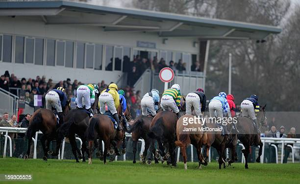 Horses and rides pass the grand stand during the Connoll's Red Mills National Hunt Novices Hurdle Race at Huntingdon Racecourse on January 11 2013 in...