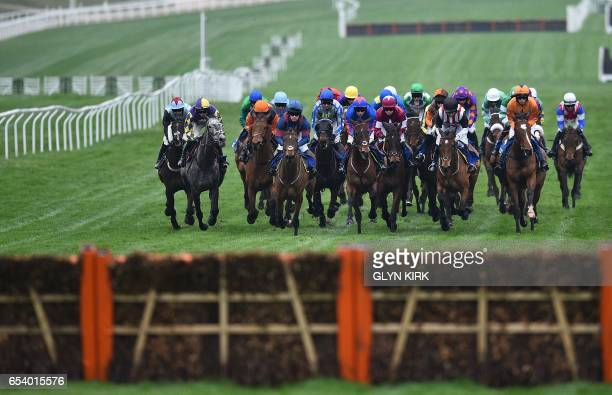 Horses approach a hurdle as they run in The Pertemps Network Final Handicap Hurdle Race on the third day of the Cheltenham Festival horse racing...