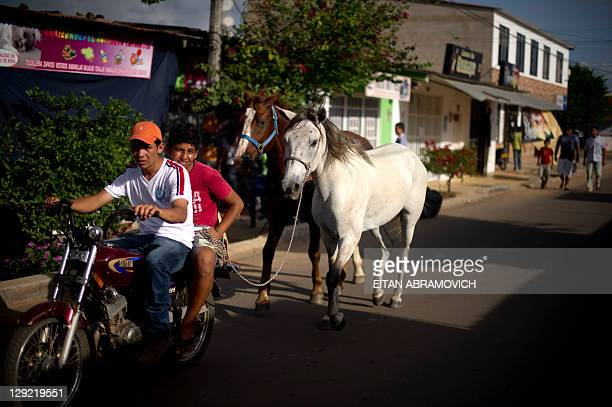 Horses are pulled by two young men riding a motorcycle in Puerto Gaitan Meta department eastern Colombia on October 8 2011 The oil bonanza that goes...