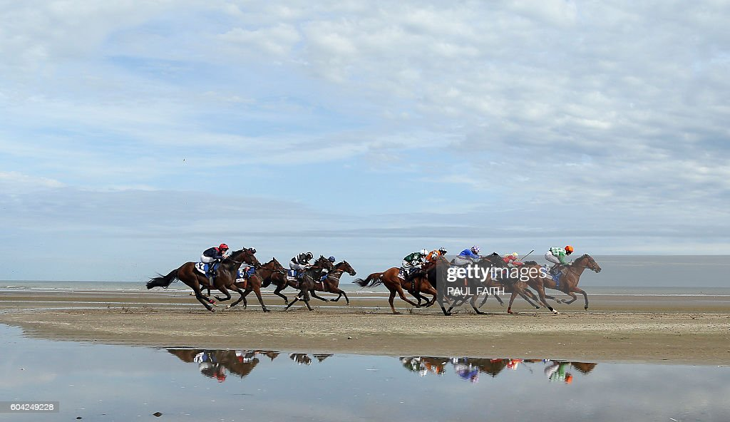 TOPSHOT - Horses compete on the course on Laytown beach in County Meath on the east coast of Ireland on September 13, 2016 during the Laytown Strand horse races. The Laytown Strand races are the only races in the Irish and English calendar that are run on a beach. / AFP / PAUL