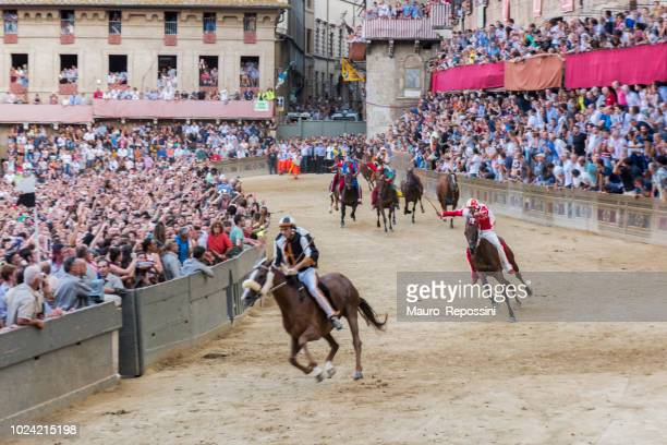 """horses competing at """"piazza di campo"""" during the """"palio di siena"""" at siena city, italy. - siena province stock pictures, royalty-free photos & images"""
