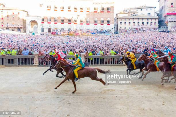 """horses competing during the first lap of the 2019 palio di siena in the """"piazza di campo"""" at the city of siena in tuscany, italy. - siena province stock pictures, royalty-free photos & images"""