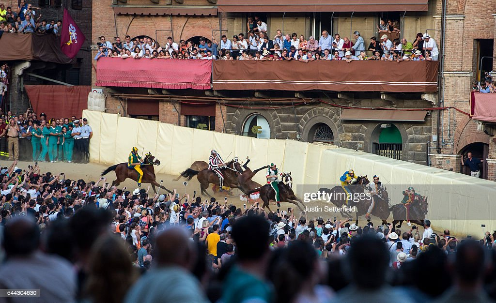 Horses fall on the bend during the historical Italian horse race of the Palio Di Siena on July 02, 2016 in Siena, Italy. The Palio di Siena, known locally simply as Il Palio, is a horse race that is held twice each year on 2 July and 16 August, in Siena, Italy. Ten horses representing ten of the seventeen districts 'Contradas' with jockeys 'Fantini' riding bareback compete during a three lap race around a makeshift course built in the 'Piazza del Campo' the city's central square to win the Palio banner. The Palio di Siena is more than a simple horse race. It is the culmination of ongoing rivalry and competition between the contrade. The lead-up and the day of the race are invested with passion and pride. The Palio held on 2 July is named Palio di Provenzano, in honour of the Madonna of Provenzano, a Marian devotion particular to Siena which developed around an icon from the Terzo Camollia. The race winner is awarded a banner of painted silk, or palio, which is hand-painted by a different artist for each race.