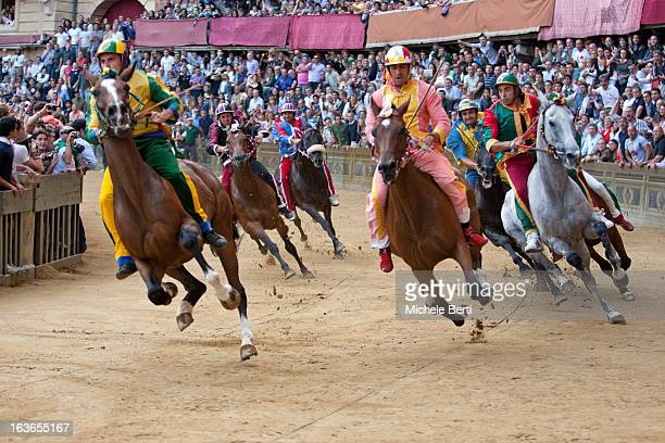 CONTENT] Horses of contrade Pantera Valdimontone Bruco Civetta Drago and Tartuca approaching at the dangerous corner of San Martino in 'Piazza del...