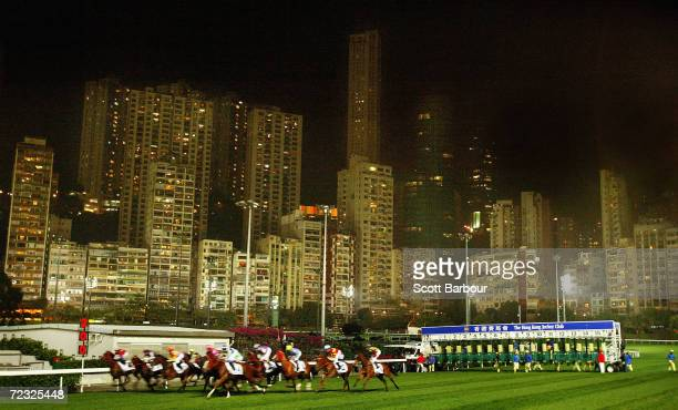 Horses race past the city skyline during race 7 of the International Jockeys' Championship Races held at Happy Valley Racecourse December 10 2003 in...