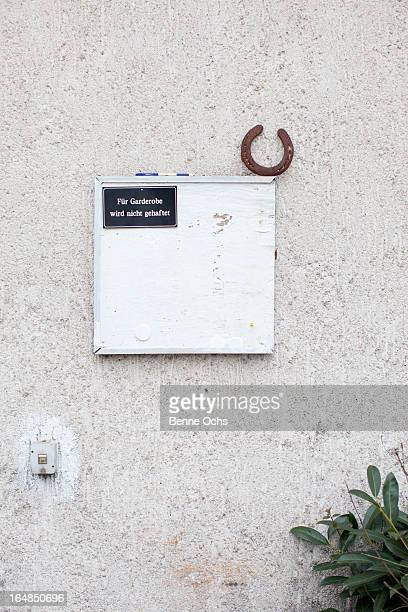 A horseshoe and a sign hanging on a wall saying ''not responsible for belongings''