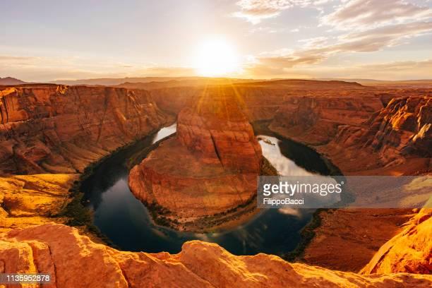 curvatura em ferradura durante o por do sol-rio de colorado, o arizona - planalto - fotografias e filmes do acervo