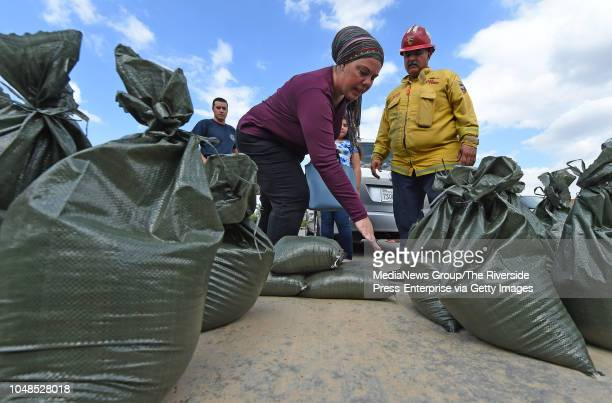 Horsethief Canyon resident Jennifer Hom asks Cal Fire Captain Aldo Aleman how to properly use sandbags at the Sycamore Creek fire station in Corona...