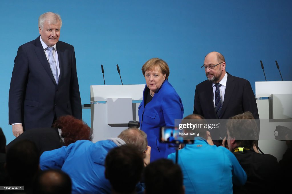 Horst Seehofer, leader of the Christian Social Union (CSU) party, left, Angela Merkel, Germany's chancellor, center, and Martin Schulz, leader of the Social Democrat Party (SPD), pose for photographs at the end of a news conference following overnight coalition negotiations, at the SPD headquarters in Berlin, Germany, on Friday, Jan. 12, 2018. After a marathon of more than 24 hours of talks to end Germanys political gridlock, leaders of Merkels Christian Democratic Union, her Bavarian sister party and the Social Democrats hammered out a 28-page agreement. Photographer: Krisztian Bocsi/Bloomberg via Getty Images