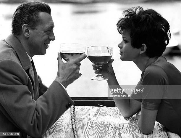 Horst Tappert*Schauspieler Dmit Uschi Glas an einem Tisch beidehaben ihr Gläser zum Anstossen erhoben 1970