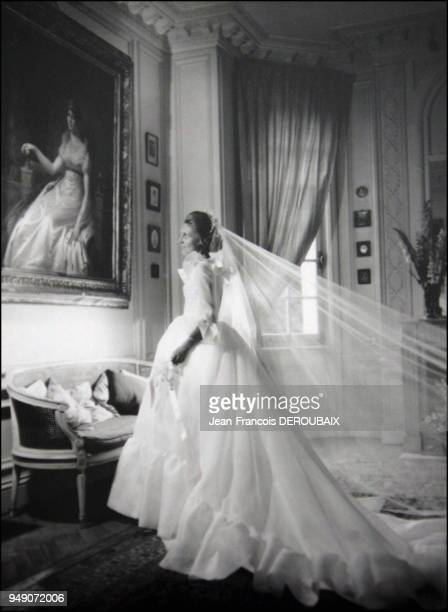 Hortense in her wedding dress poses in front of a portrait of empress Josephine
