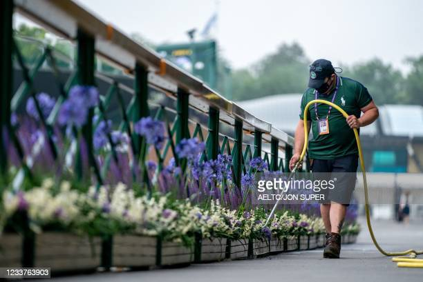 Horticulture staff watering the planters outside the Clubhouse on the fifth day of the 2021 Wimbledon Championships at The All England Tennis Club in...