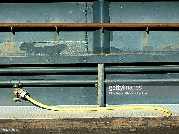 Hose Attached To Pipe On Wall In Factory