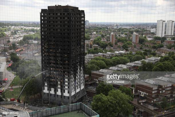 A hose continues to douse the fire at Grenfell Tower on June 15 2017 in London England At least 17 people have been confirmed dead and dozens missing...