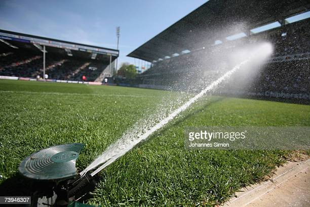A hose pipe jets water over the pitch during halftime in the Second Bundesliga match between SC Freiburg and Carl Zeiss Jena at the Badenova stadium...