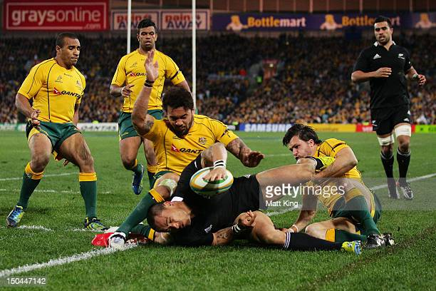 Hosea Gear of the All Blacks is tackled into touch just short of the line by Digby Ioane and Adam AshleyCooper of the Wallabies during The Rugby...