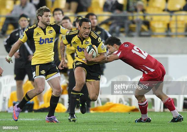 Hosea Gear of the Hurricanes is tackled by Anthony Faingaa of the Reds during the round 13 Super 14 match between the Hurricanes and the Reds at...