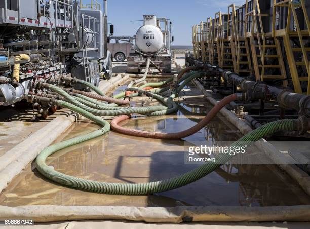 Hoses carry water to hydraulic fracking machinery at a Royal Dutch Shell Plc site near Mentone Texas US on Thursday March 2 2017 Exxon Mobil Corp...