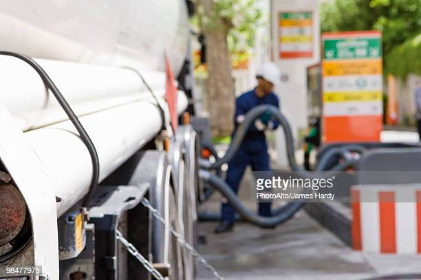 Hoses connected to fuel tanker outlets transferring fuel to gas station storage tanks