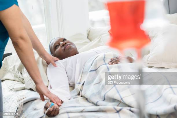 hospice nurse checks on senior female patient - hospice stock pictures, royalty-free photos & images