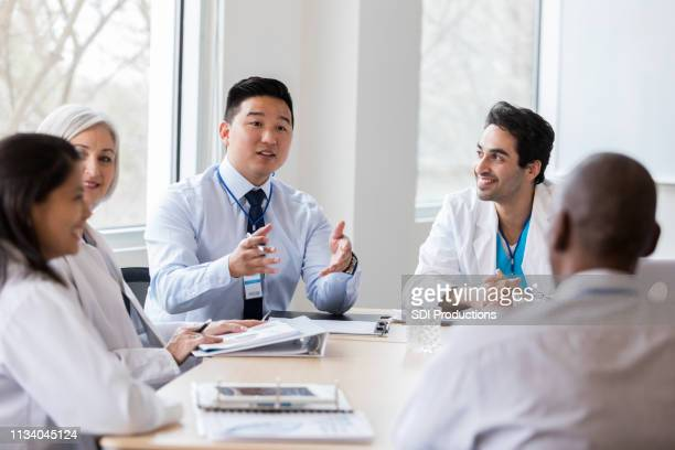hospital administrator conducts staff meeting - administrator stock pictures, royalty-free photos & images