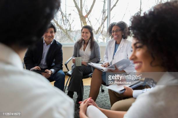 hospital administrator facilitates staff meeting - group of doctors stock pictures, royalty-free photos & images