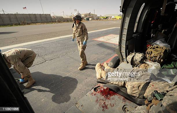 Hospital ambulance crew prepare to carry a wounded US army soldier from a Blackhawk helicopter from Company C 1st Battalion 52nd Aviation Regiment...